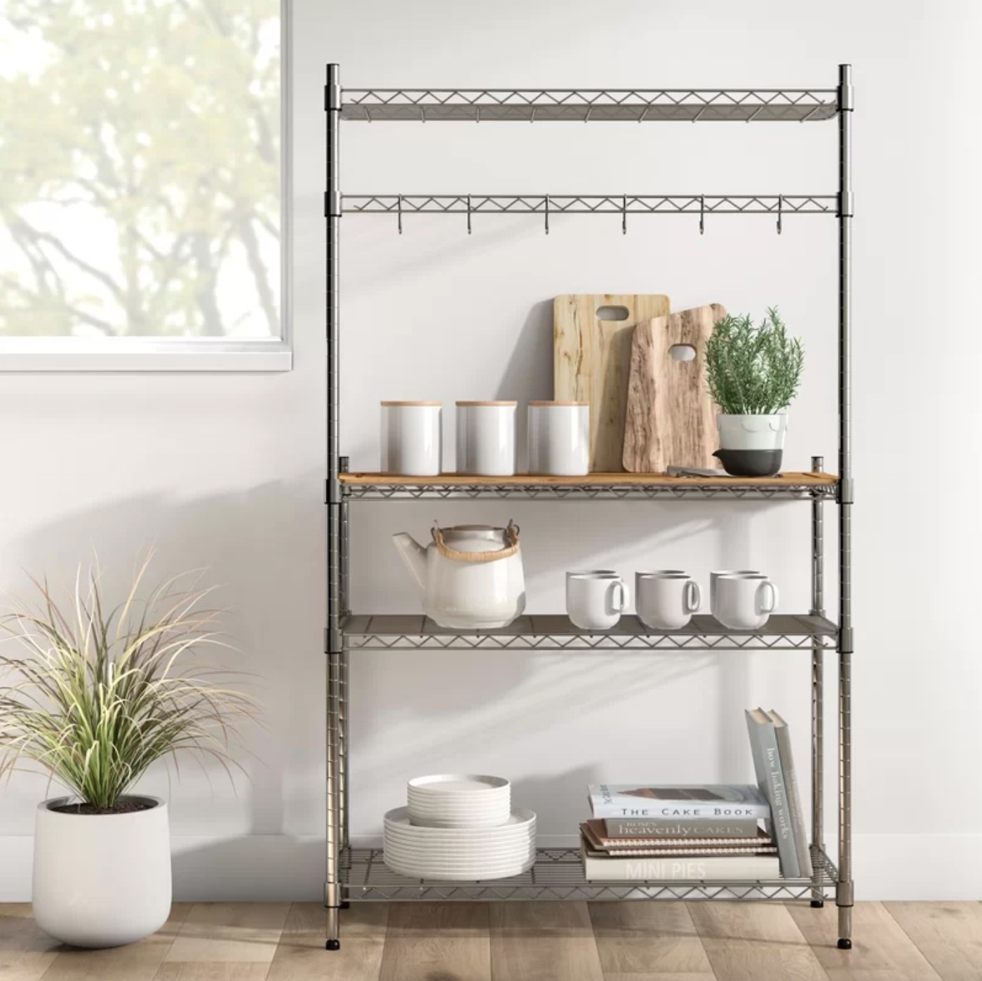 The chrome baker's rack holding coffee mugs, plates, books, and cutting boards