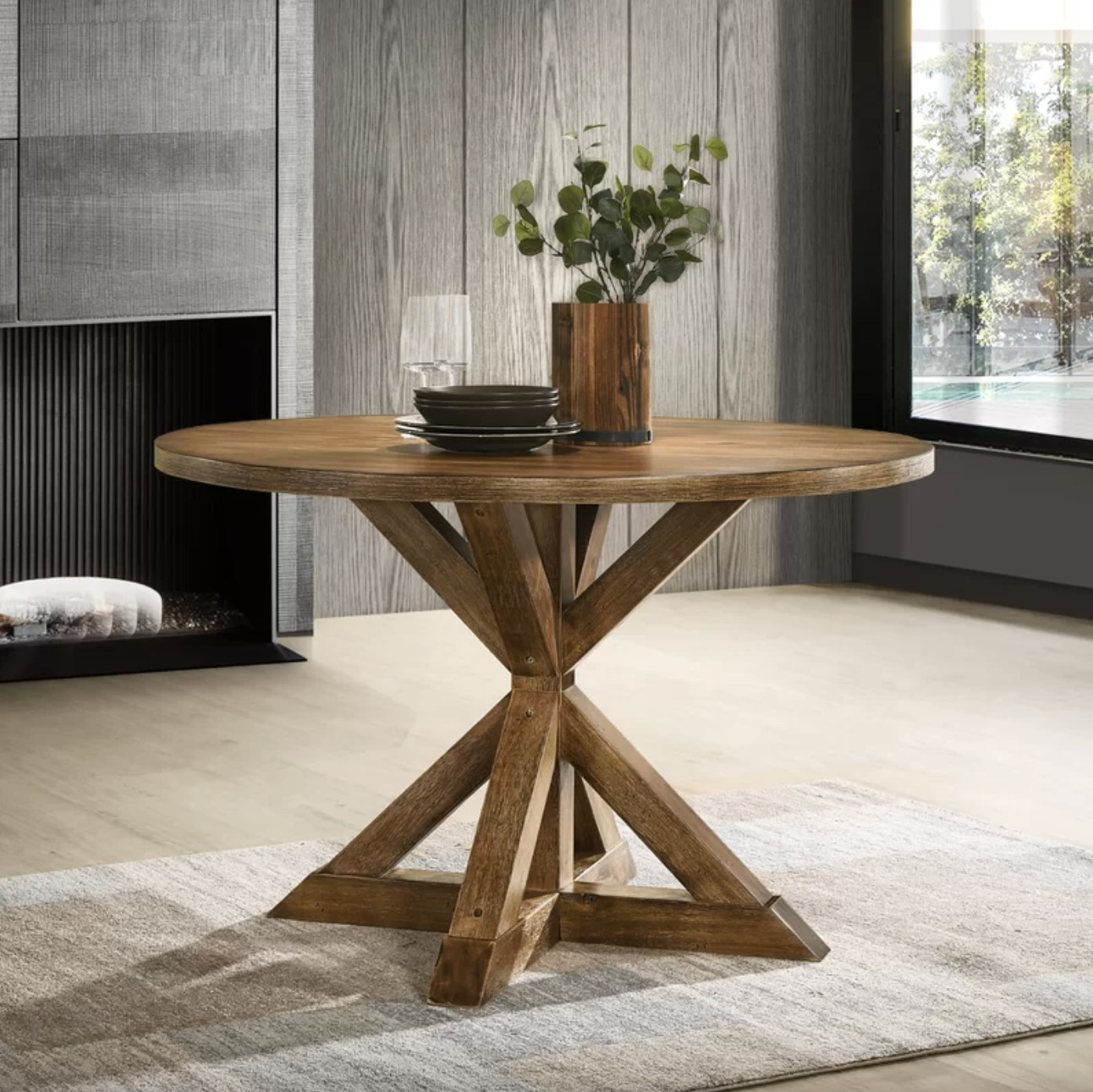The dining table in natural/ ash holding plates, wine glasses, and vase of eucalyptus flowers