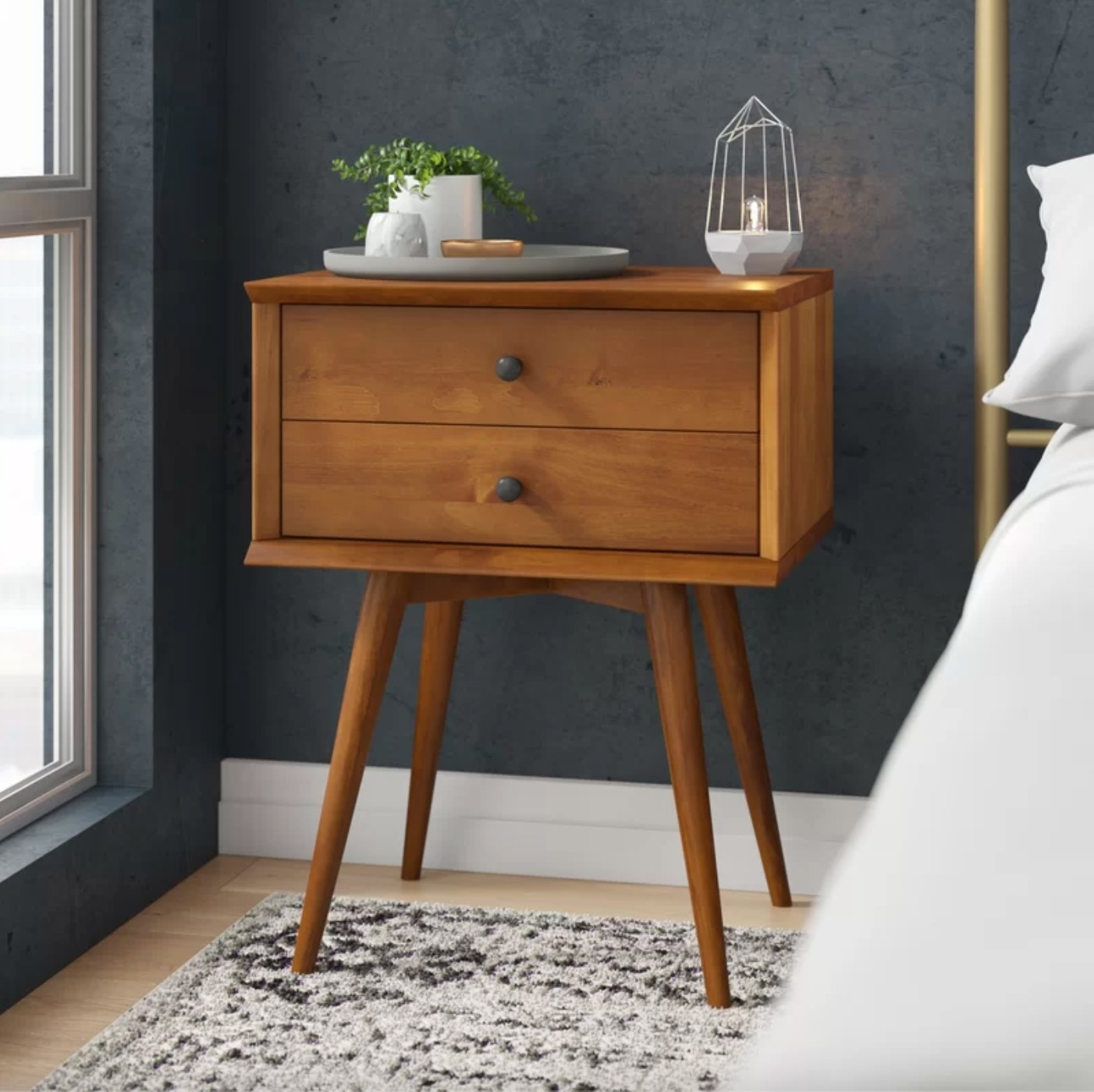 The solid wood double drawer nightstand in Castanho holding a plant and lamp