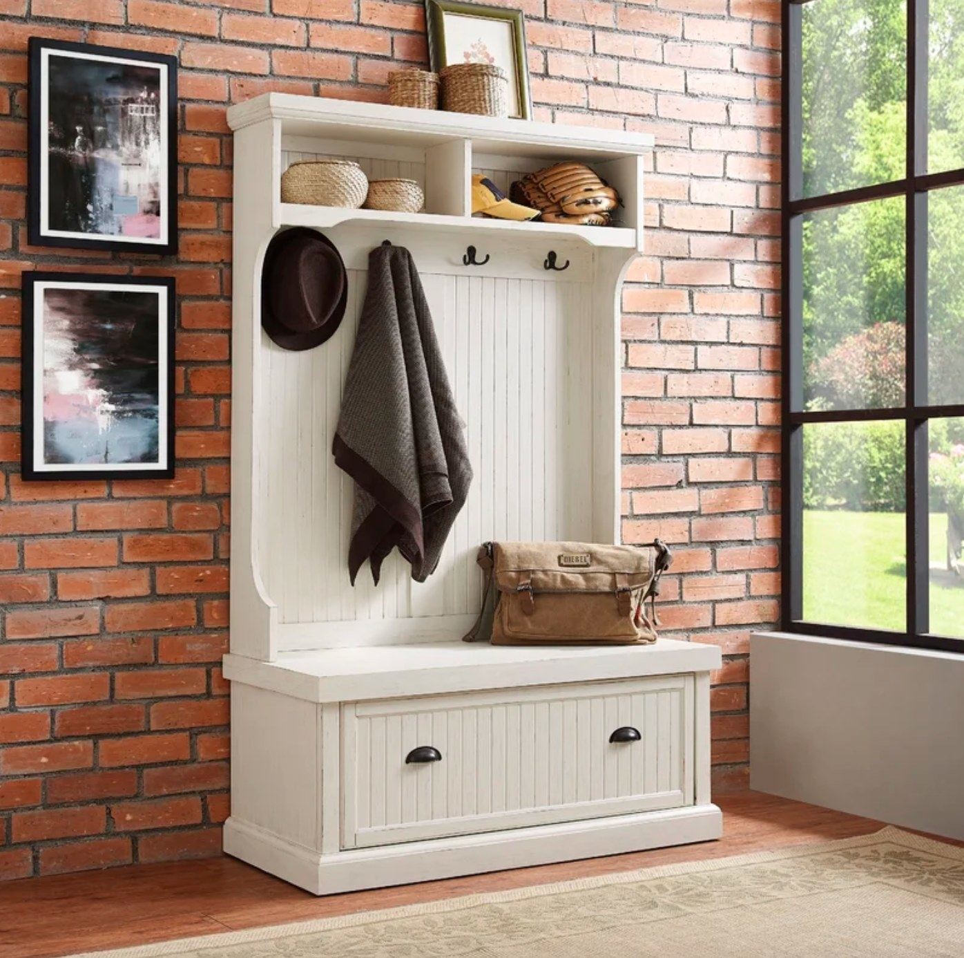 The hall tree with coat and shoe storage in distressed white