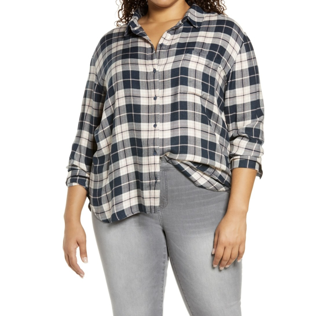 Model is wearing a black and white plaid top and grey denim jeans