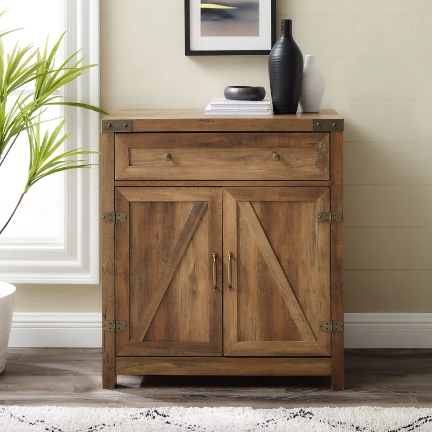 The two-door accent cabinet in reclaimed barnwood holding two vases
