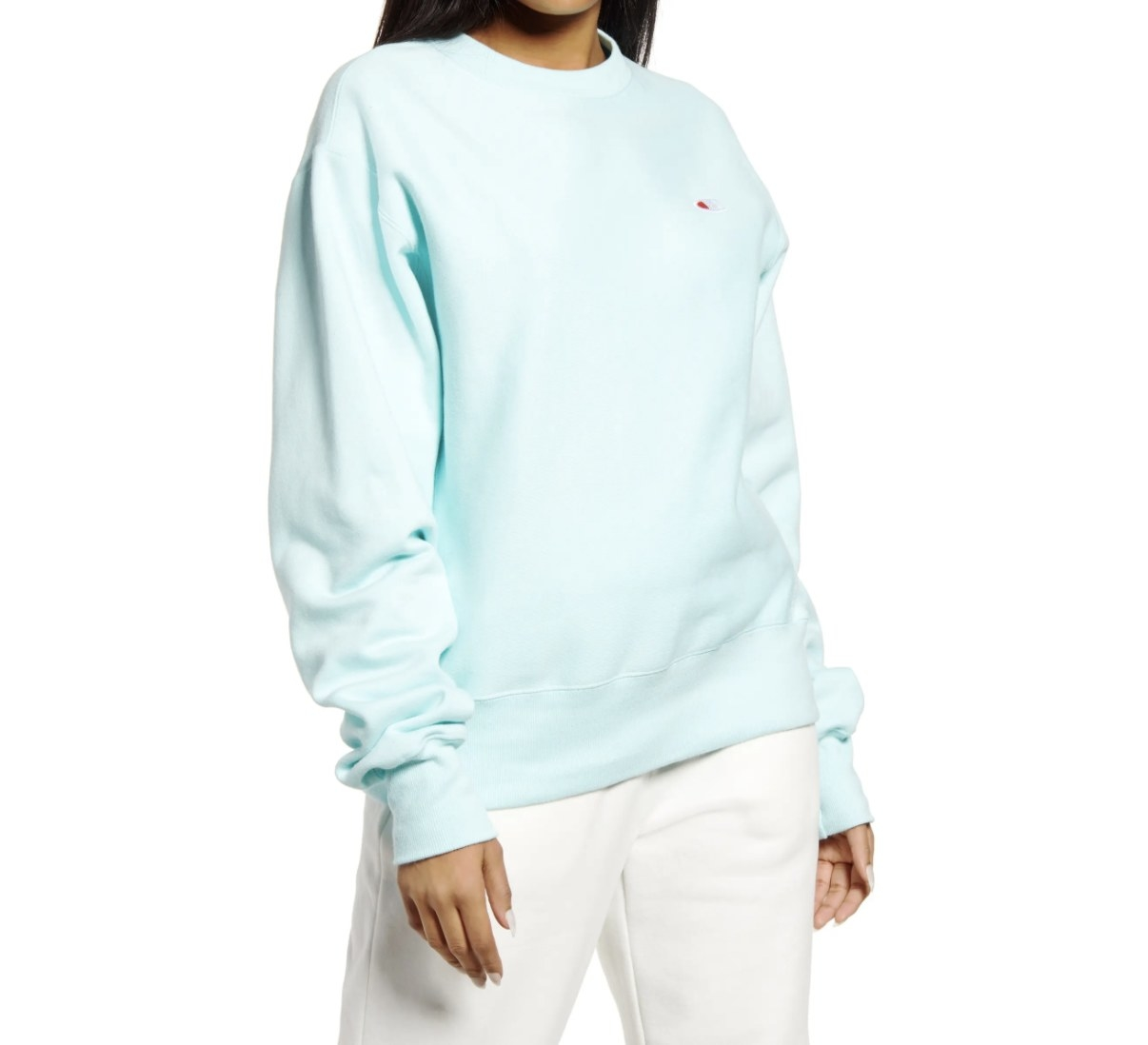 Model is wearing a light blue sweater and white pants