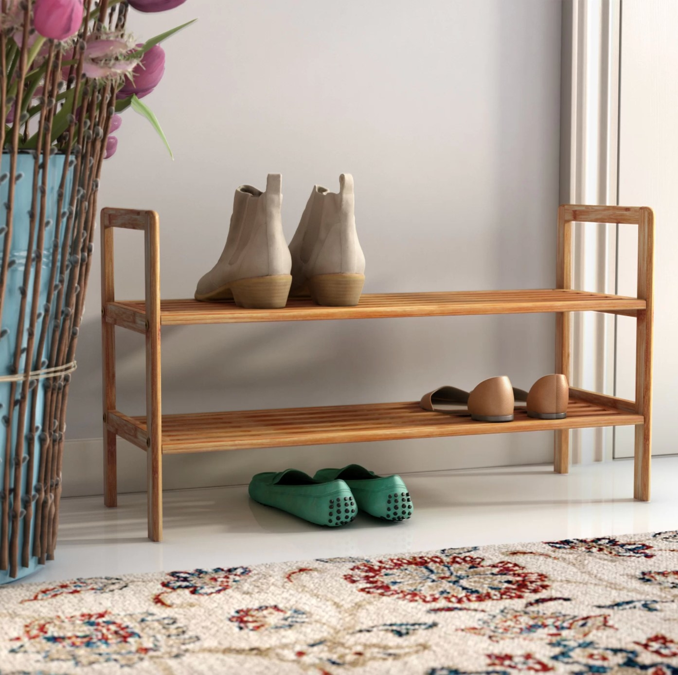 The two-tier shoe rack in bamboo holding flats and boots