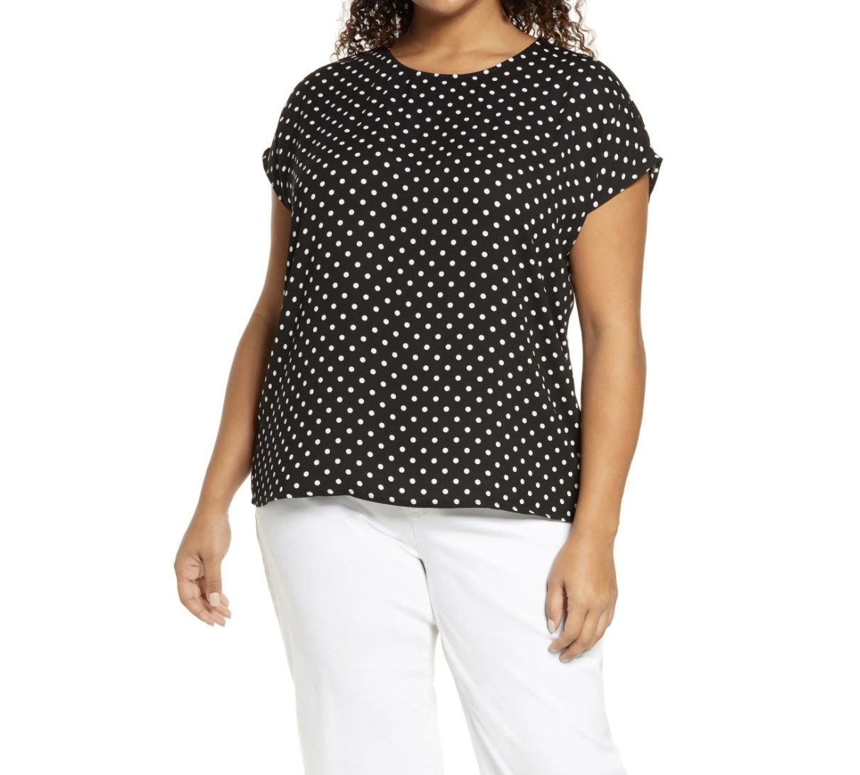 Model is wearing a black polka dot top and white pants