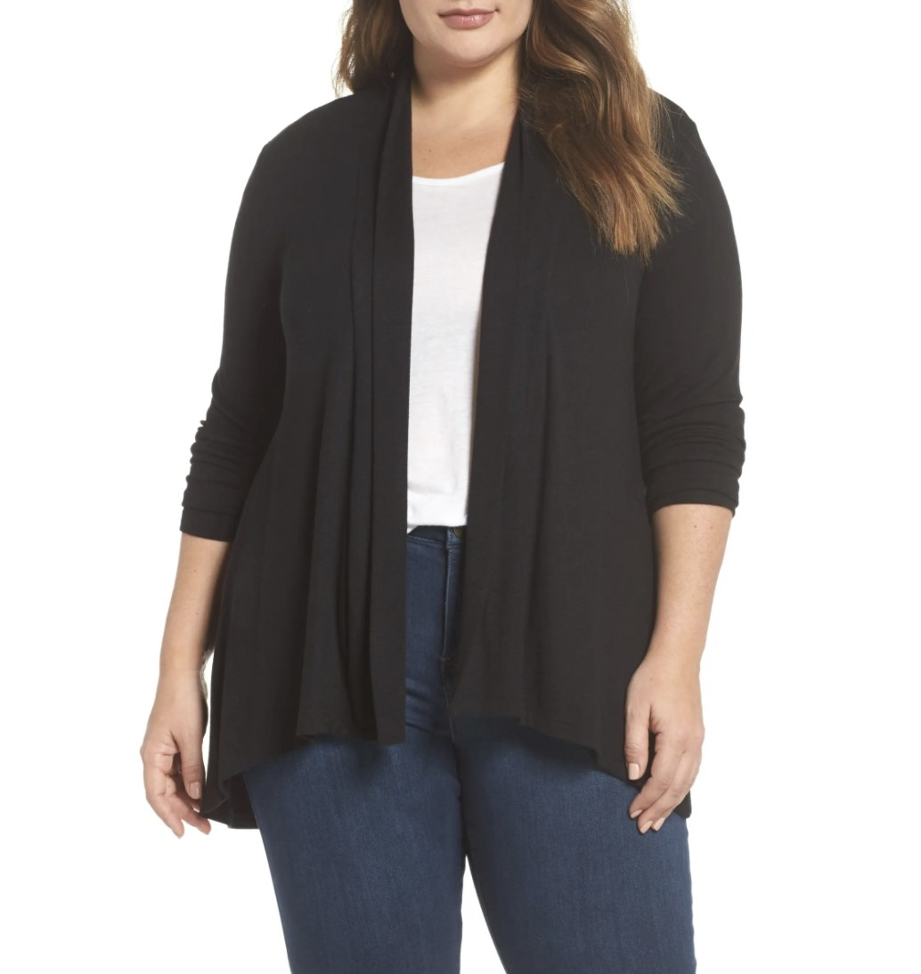 Model is wearing a black cardigan, white top, and blue jeans