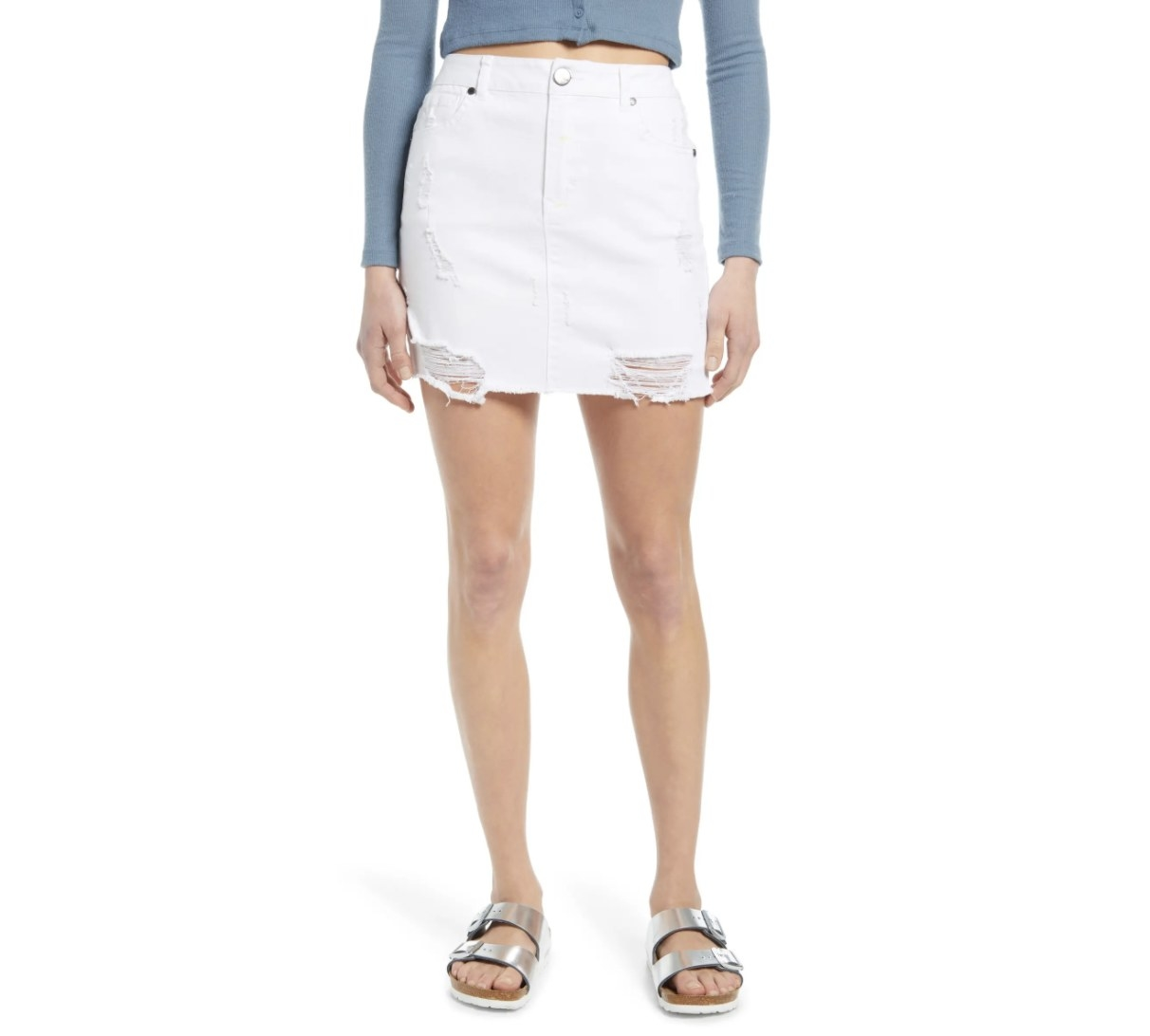 Model is wearing a white denim skirt and metallic sandals