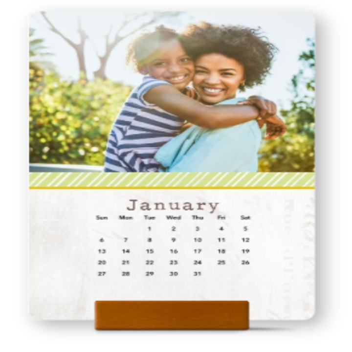 vertical January calendar page with a photo of a model holding a child, propped on a wood block