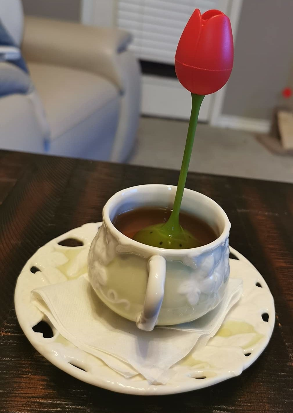 the tall tulip-shaped infuser, which has a red flower design and a tea-dispensing green base, in a reviewer's mug