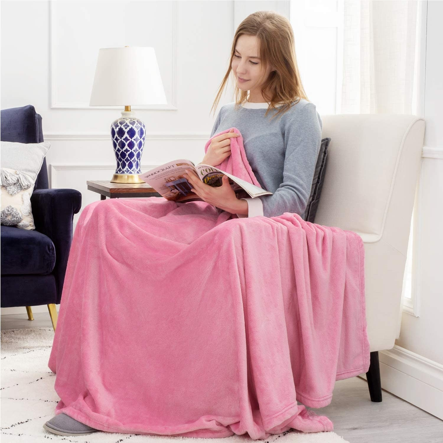 Model reading in a chair with pink blanket draped over them