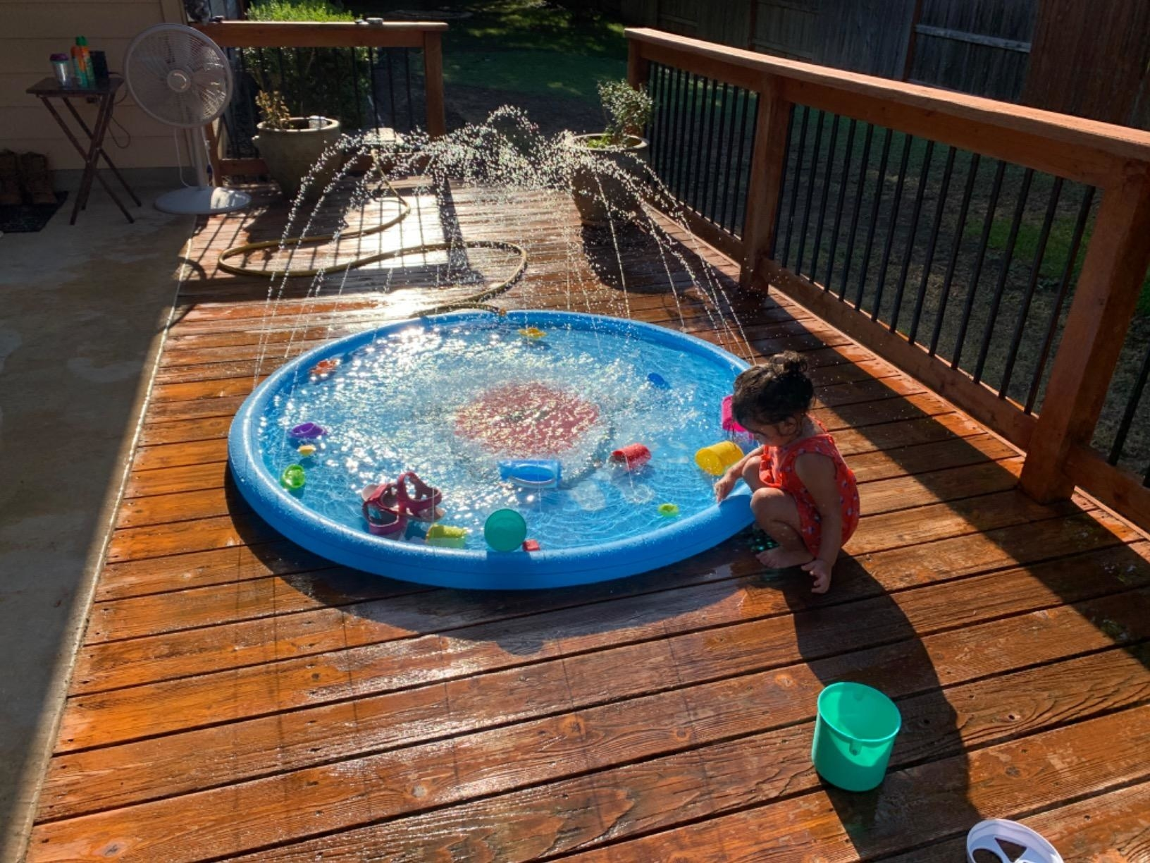 The splash pad, which is circular, and has streams of water that shoot out from various points around the rim of the pad
