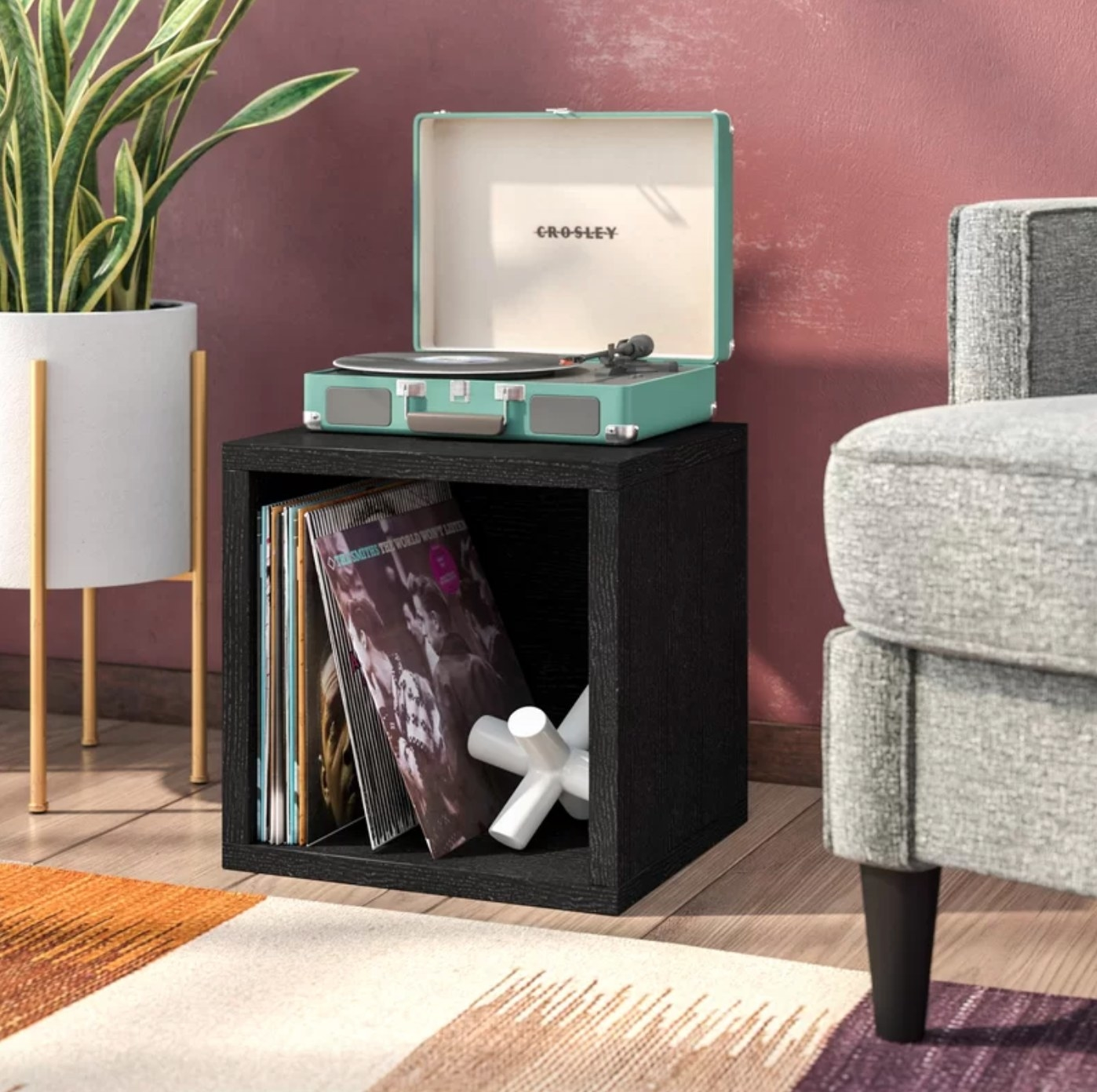 The stackable multimedia shelf in black holding a blue Crosley record player and records