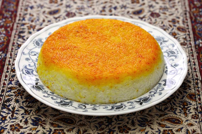 A perfectly smooth mound of rice, browned on the top, on a floral plate which sits on a patterned tablecloth