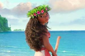 Moana standing on the beach and holding an oar
