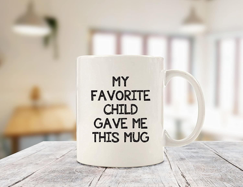"white mug that reads ""my favorite child gave me this mug"""