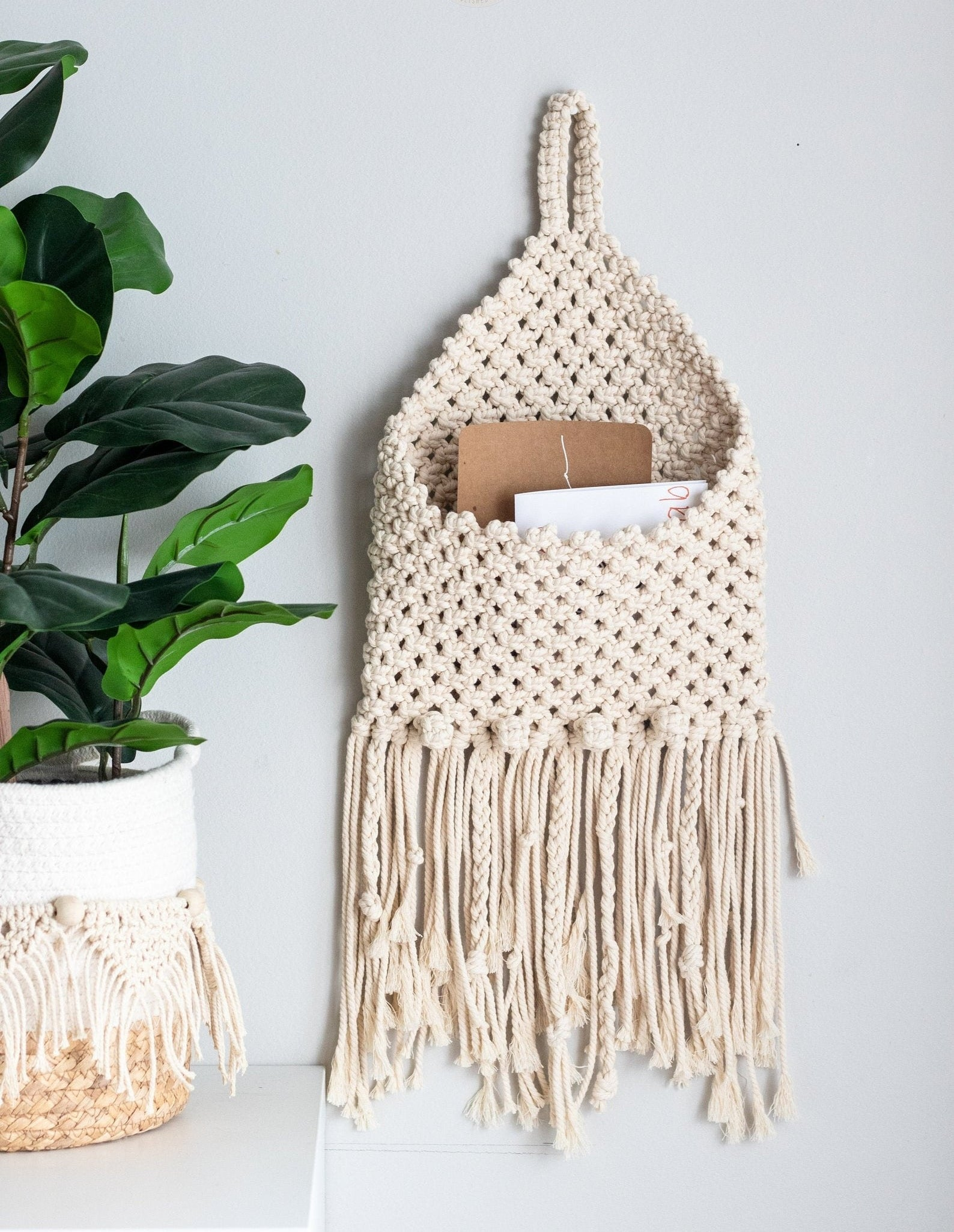 the cream-colored macrame envelope holder holding a few cards
