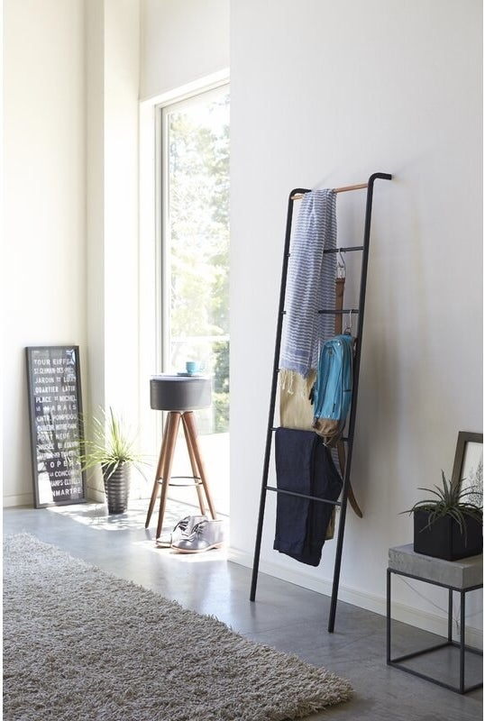 Black blanket ladder propped up against a wall with accessories hung on it