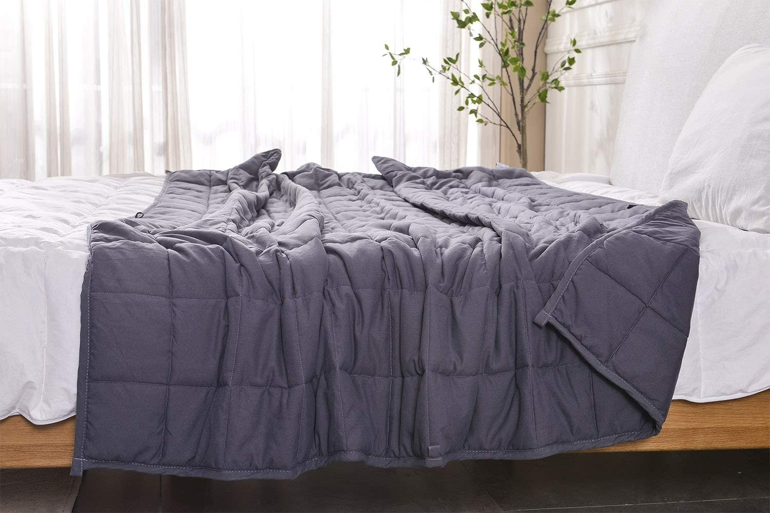the AN cooling weighted blanket draped loosely on a bed with white sheets