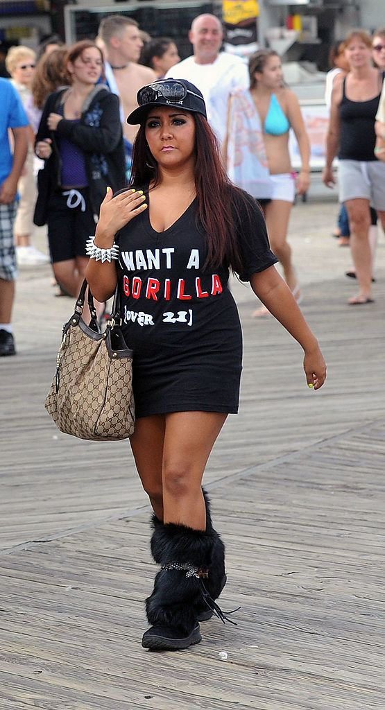 Snooki on a boardwalk wearing a graphic tee, tight skirt, furry boots, and a baseball cap