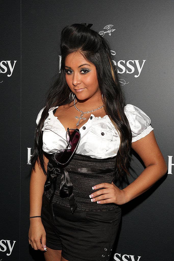 Snooki wearing a satin blouse, and shorts and a boufant hairdo