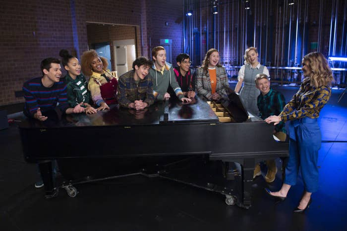 The cast standing around a piano