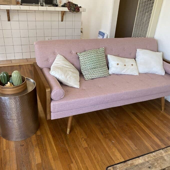 The fabric sofa in light pink with wooden frame and pin legs