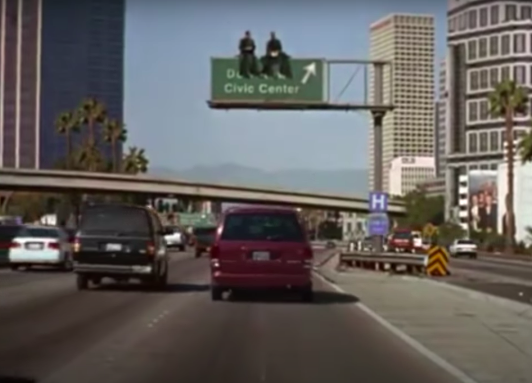 """Nicolas Cage and Andre Braugher sitting on a road sign in """"City of Angels"""""""