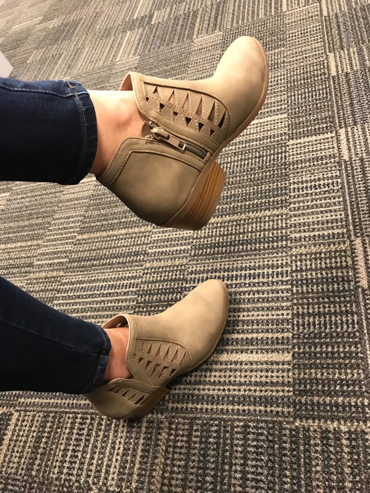 reviewer in tan booties with cut-out detailing on the sides