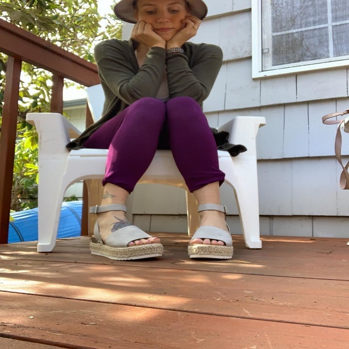 reviewer in white platform sandals while sitting on deck