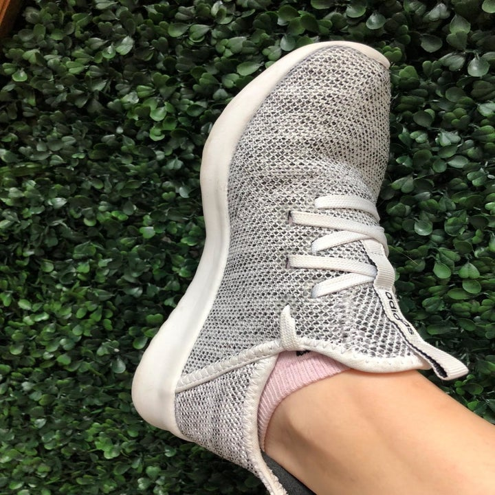 Different reviewer wears same Adidas running shoes in a gray shade