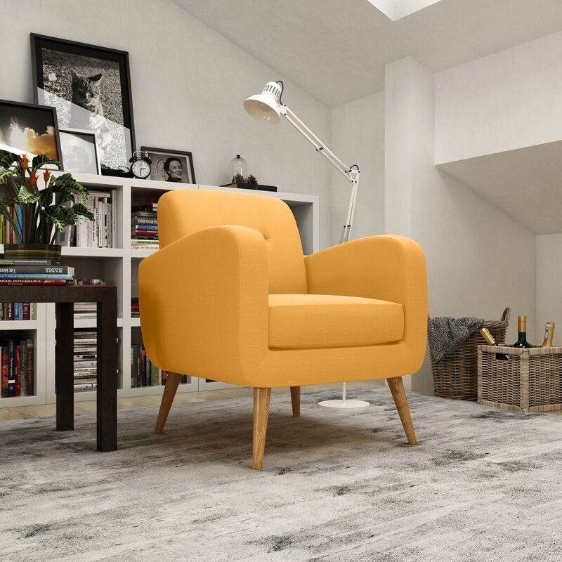 yellow armchair with wood legs in a living room