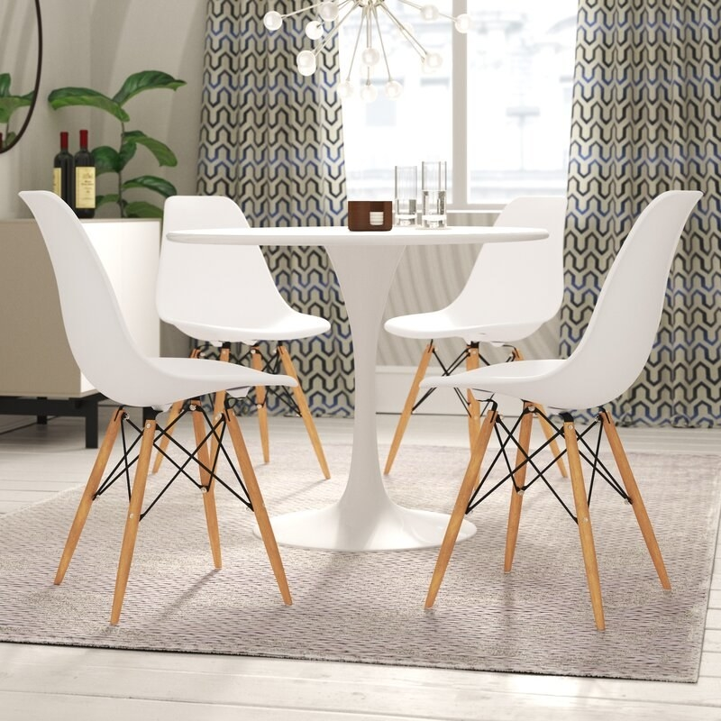 four white plastic chairs with wood legs around a round table