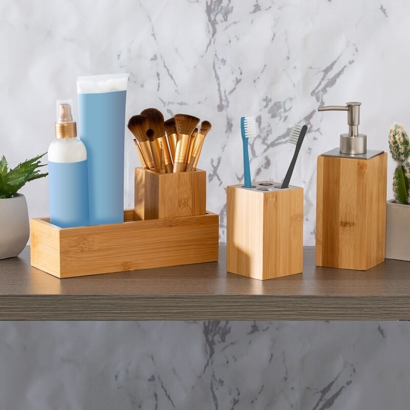 bamboo bathroom accessory set on a shelf, including a toothbrush holder, rectangular tray, accessory tray, and pump dispenser
