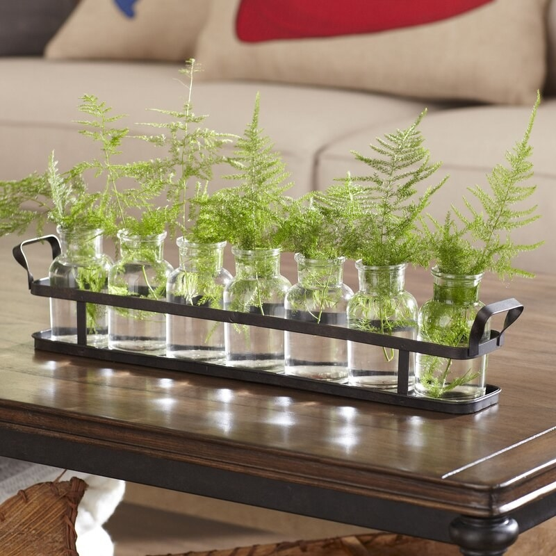 Metal tray with seven glass jars filled with greenery, sitting on a table