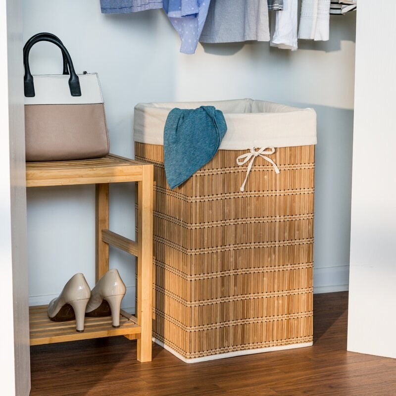 rectangular bamboo hamper with white lining inside a closet