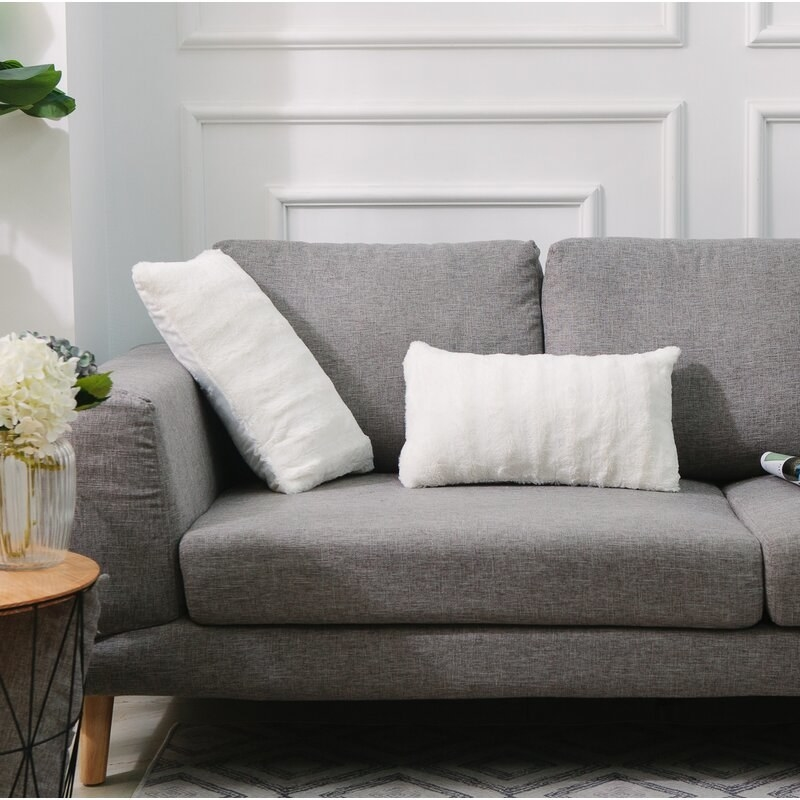 two white faux fur lumbar pillows on a grey couch