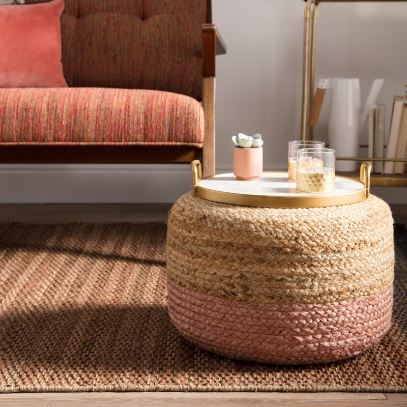 round pink and beige pouf on the floor with a tray of drinks on top