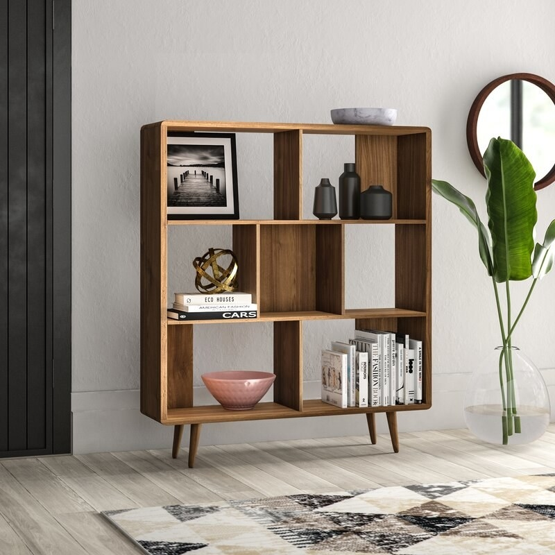 geometric wood bookcase with splayed legs, with books and decor on the shelves