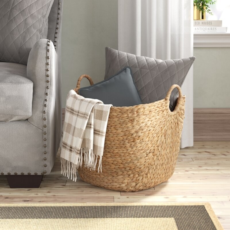 wicker basket with handles sitting on the floor filled with pillow and blankets