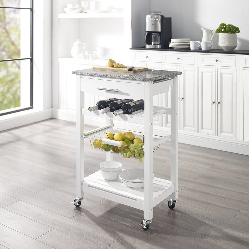 white kitchen cart with white rack, metal basket, wheels, and granite top