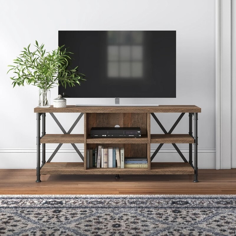TV stand with wood shelves and metal legs with a TV on top