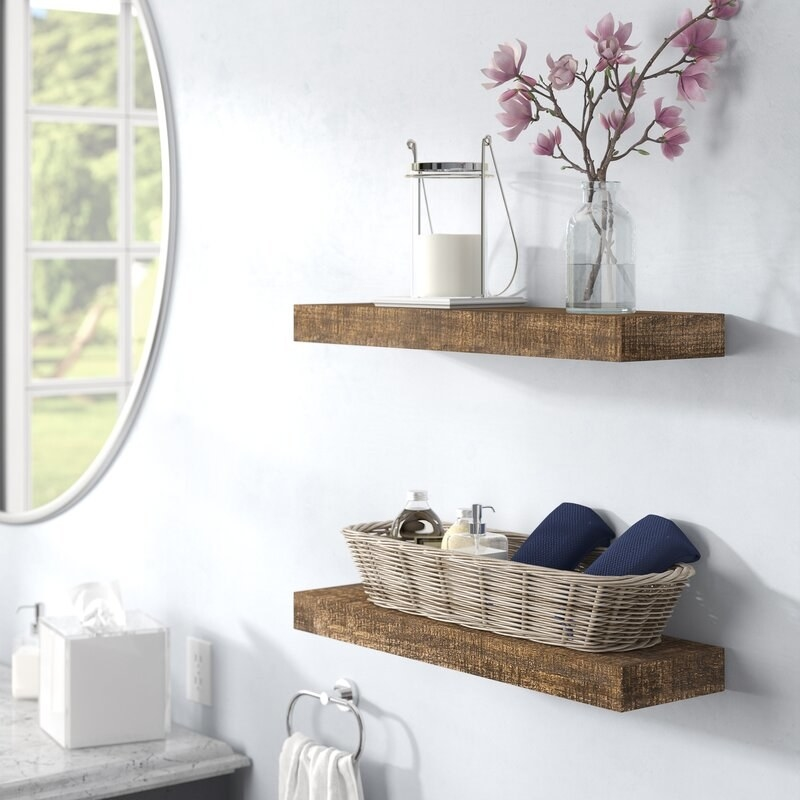 two wood floating shelves in a bathroom with accessories on top