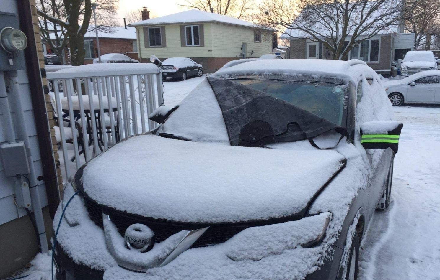the cover on a car, half off to show that there is no snow underneath