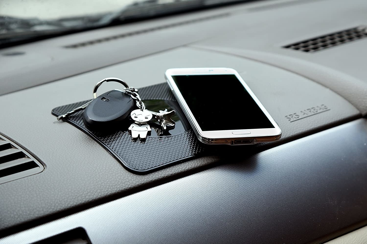 a phone and pair of keys on the mat