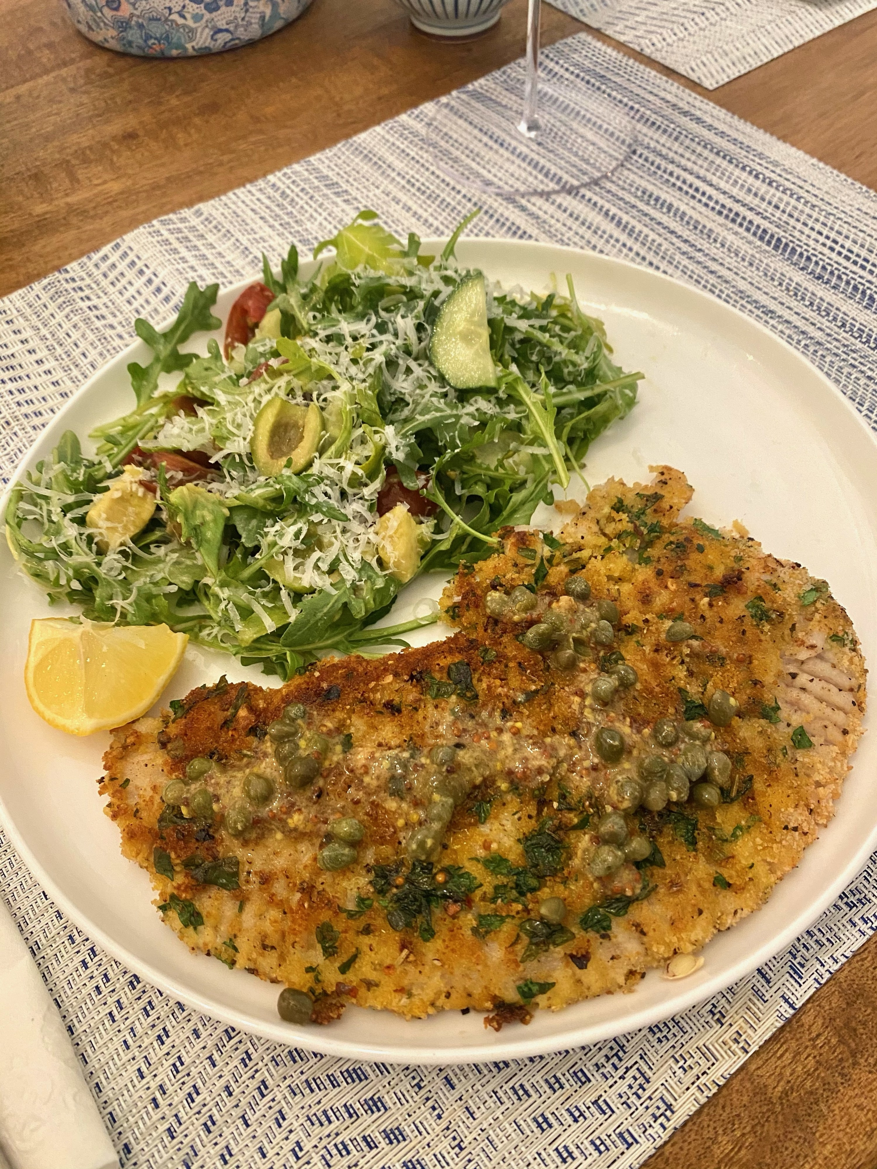 Skate wing Milanese topped with caper butter and a side salad.