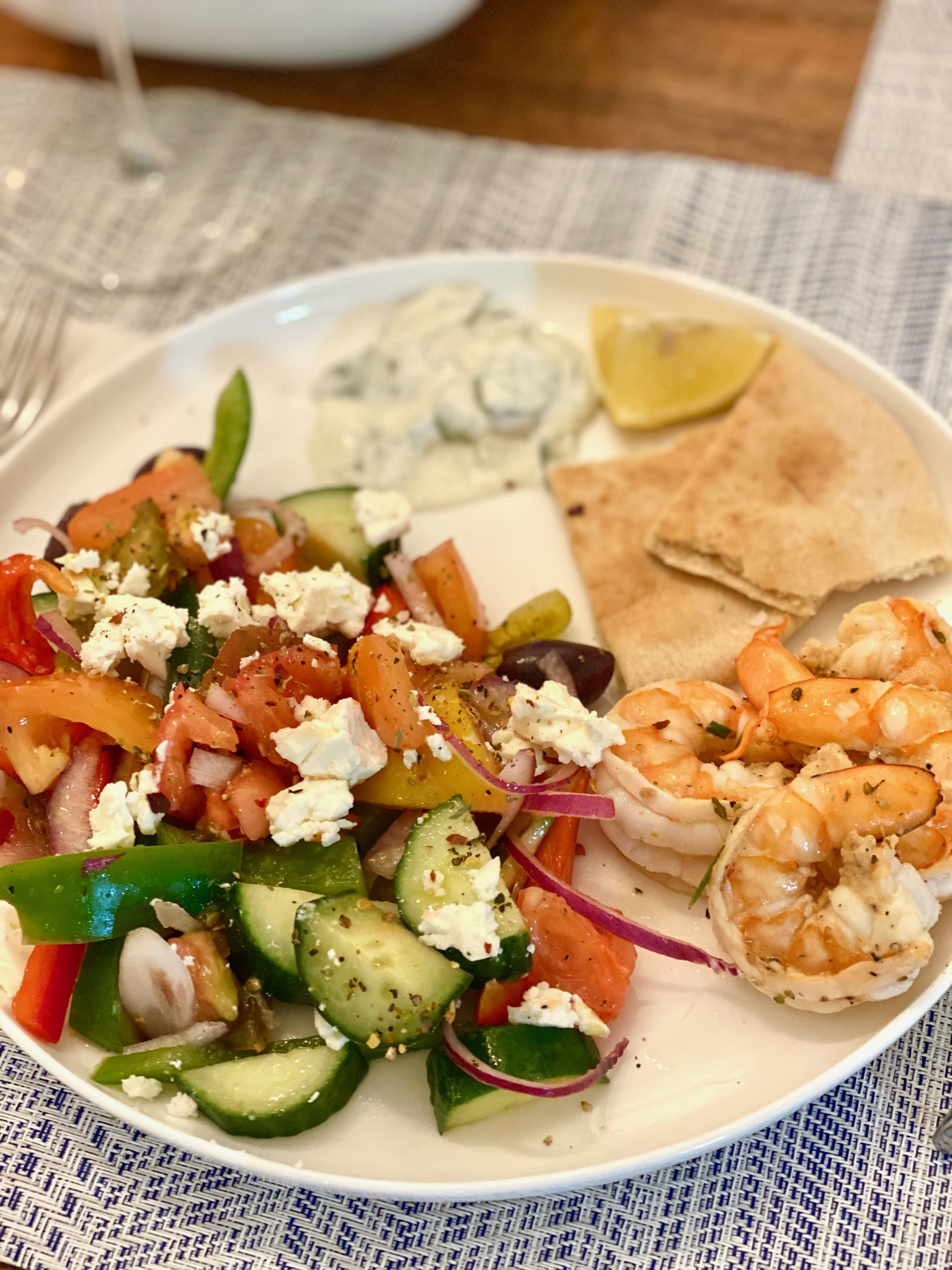 A traditional Greek salad with pita and grilled shrimp on the side.