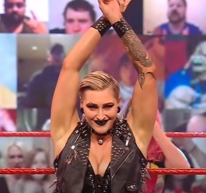 Rhea Ripley posing with arms raised