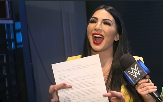 Billie Kay smiling with her mouth open while holding her job resumé