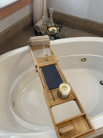 reviewer showing the bamboo tray placed on their round tub