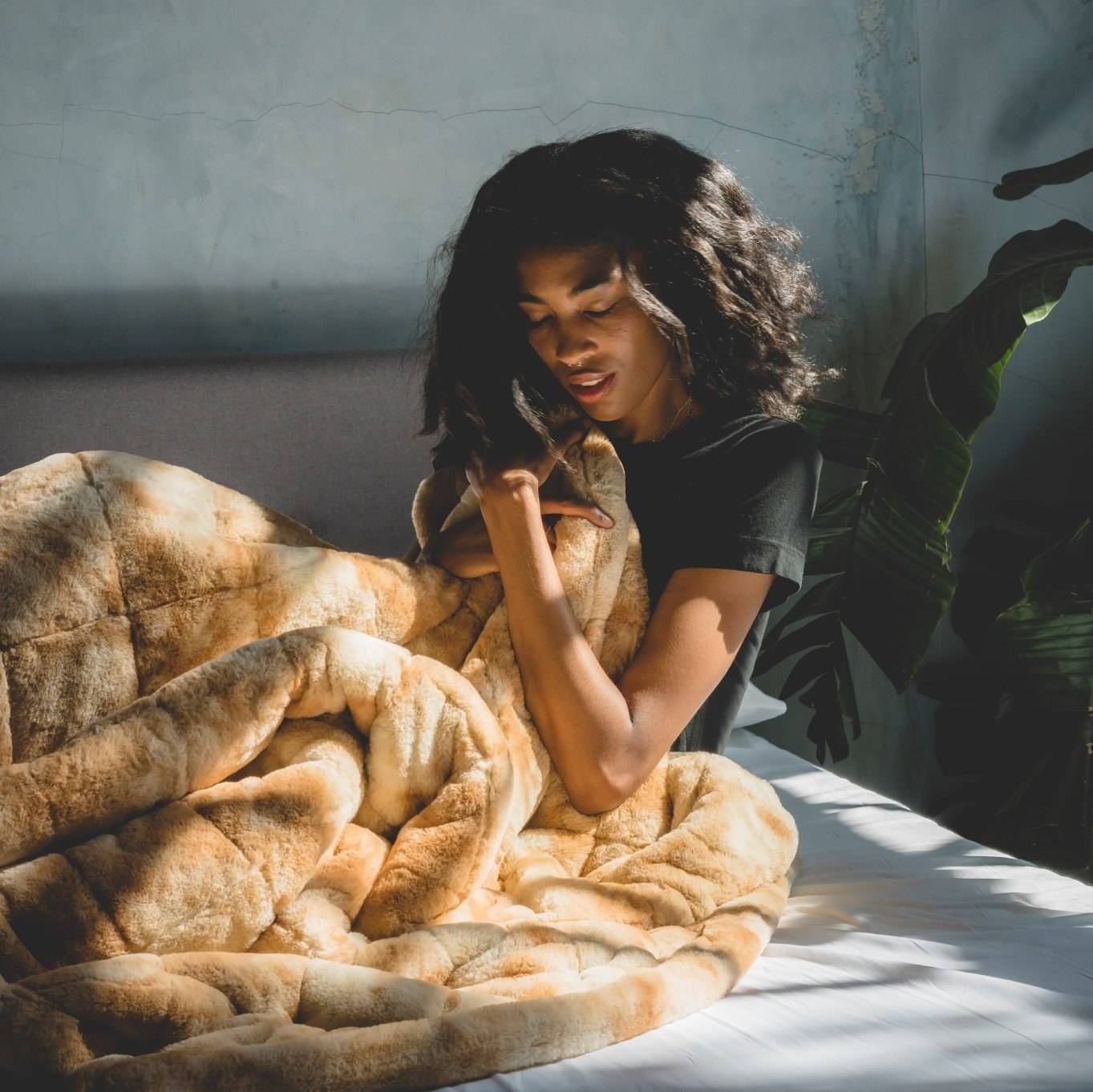 model sitting on a bed embracing the weighted blanket